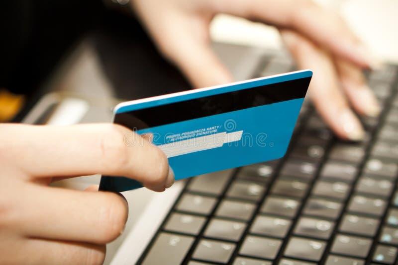 Achats en ligne avec par la carte de crédit sur l'ordinateur portatif photos libres de droits