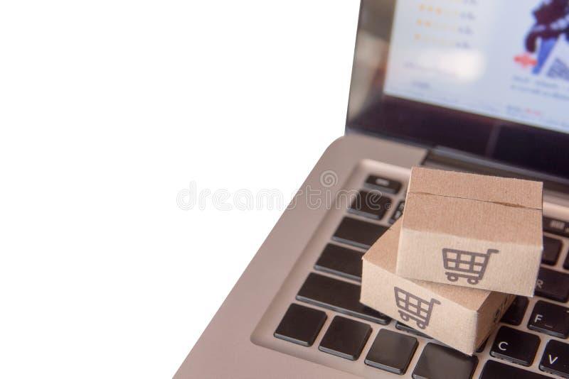 Achats en ligne : Cartons de papier ou colis avec un logo de caddie sur un clavier d'ordinateur portable Service de achat sur le  image libre de droits