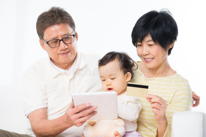 Achats en ligne de famille asiatique image stock