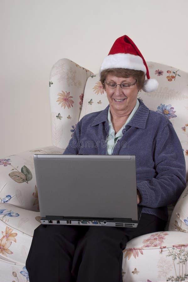 Achats en ligne de Noël de femme aîné mûr photo stock