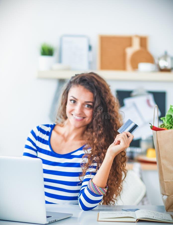 Download Achats En Ligne De Sourire De Femme Utilisant L'ordinateur Et La Carte De Crédit Dans La Cuisine Image stock - Image du heureux, tablier: 87700797