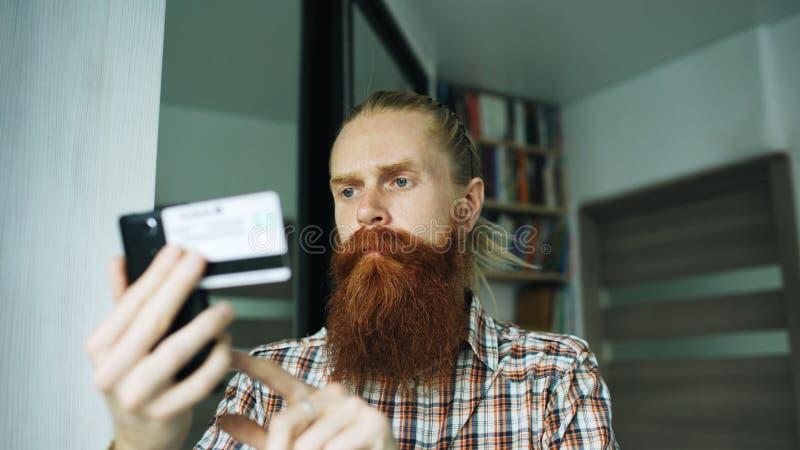 Achats en ligne et opérations bancaires d'homme barbu avec la carte de crédit utilisant le smartphone à la maison images libres de droits