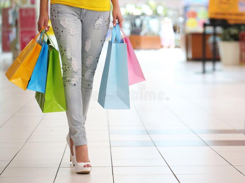 Achats Femme avec les paniers colorés dans le centre commercial photos libres de droits