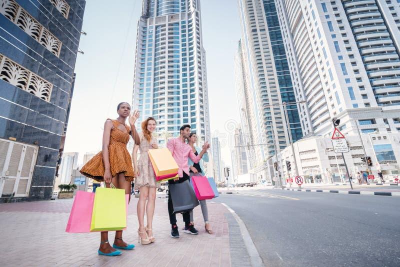 Achats grands Quatre amis tenant des paniers dans leur main photographie stock libre de droits
