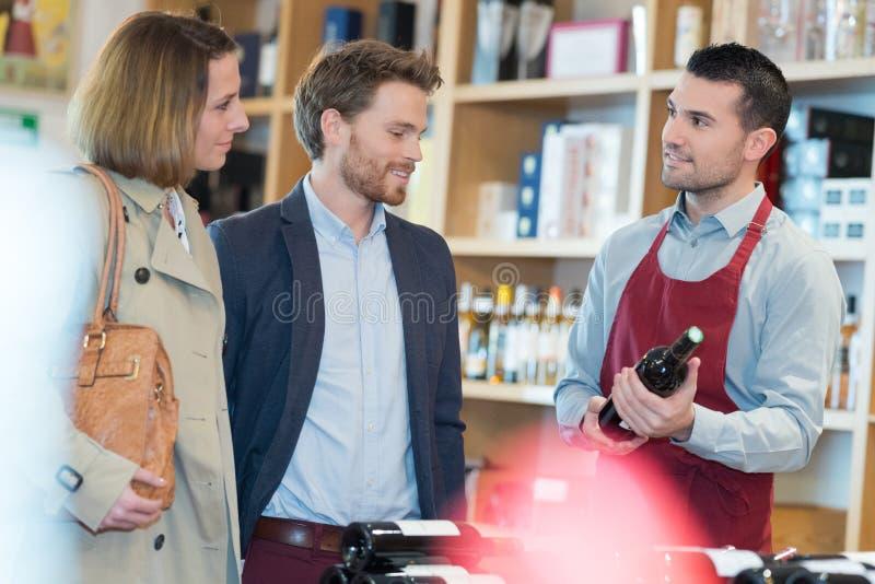 Achats heureux de couples en vins d'achats de supermarché image libre de droits