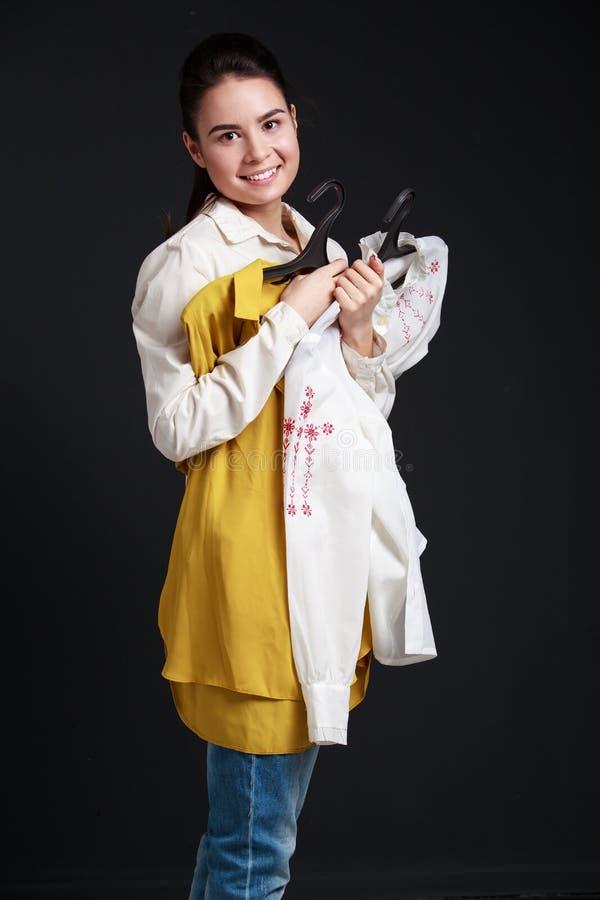 Achats Jeune femme de brune tenant deux chemises, allant essayer image libre de droits