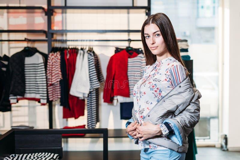 Achats, mode, style, vente, achats, affaires et les gens belle jeune femme heureuse de concept dans le magasin d'habillement Busi image stock