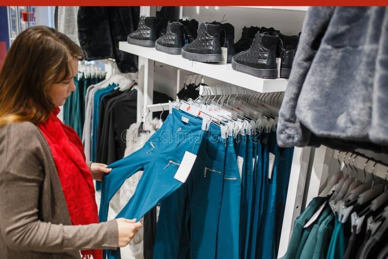 Achats, mode, vente, style et concept de personnes - jeune femme dans le manteau gris et l'écharpe rouge choisissant le pantalon  photos libres de droits