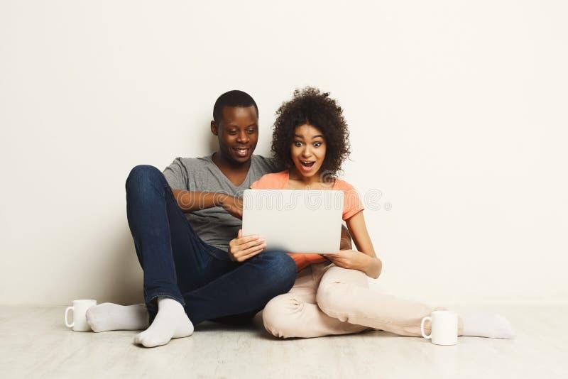 Achats noirs étonnés de couples aux ventes d'Internet sur l'ordinateur portable photos libres de droits