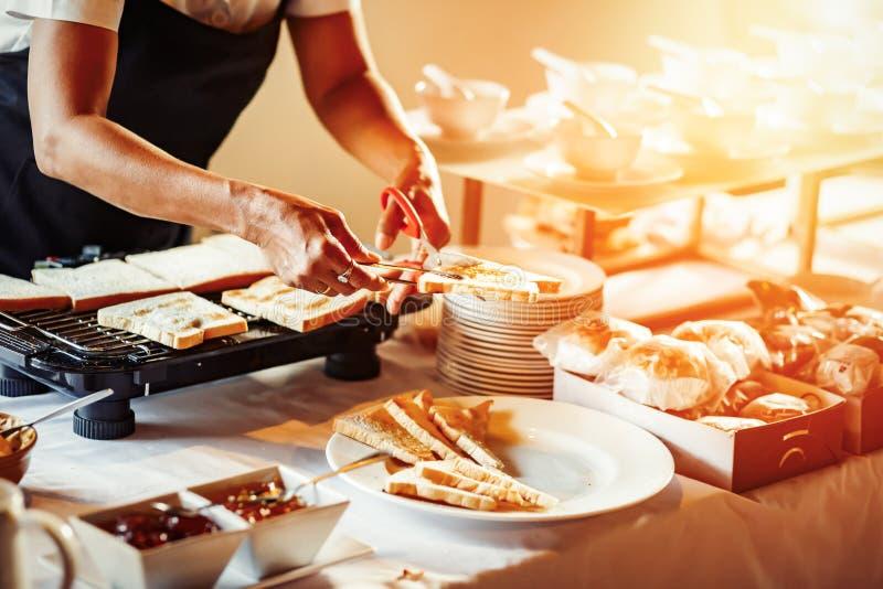 Achef schnitt Brot durch Scheren und Brot auf dem Grillen lizenzfreie stockfotografie
