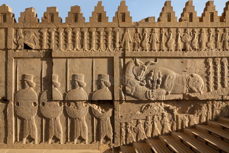 Achemenide Bas Relief Carvings del combattimento del toro e del leone accanto ai soldati in Persepolis immagini stock libere da diritti