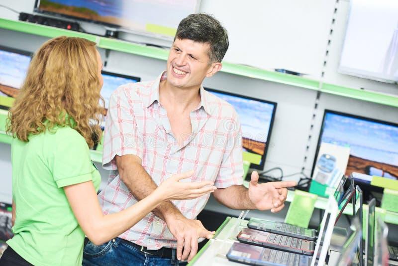 Acheteur auxiliaire d'aide de femme de vendeur choisissant l'ordinateur portable image libre de droits