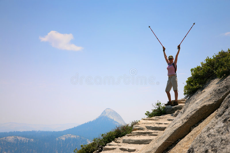 Achievement. Happy young woman standing on top of a mountain with arms rised royalty free stock images