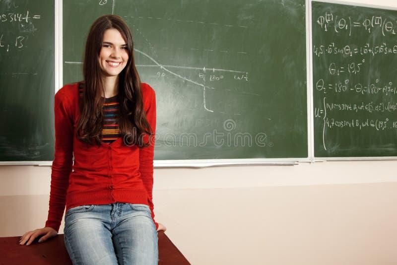 Achiever красивой предназначенной для подростков девушки высокий в классе около стола стоковая фотография