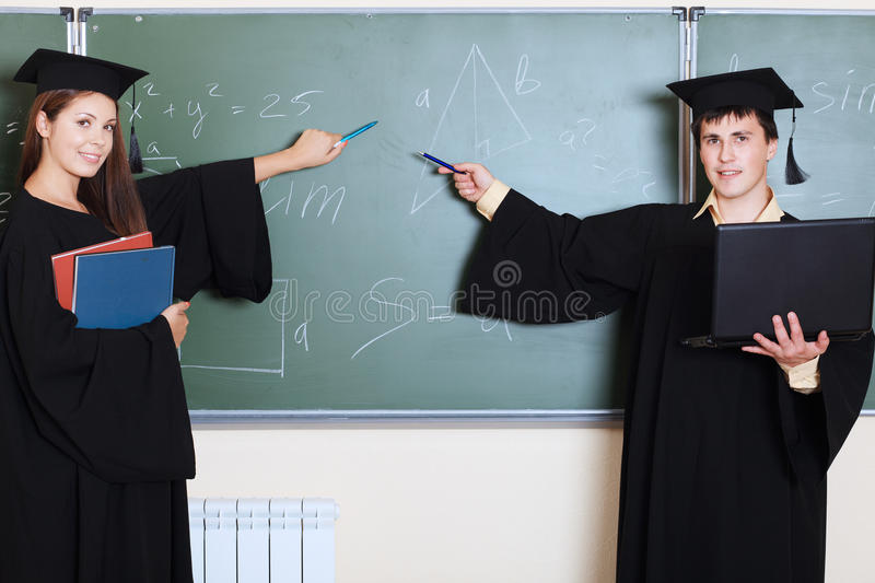 Achievers. Educational theme: graduating students in academic gown in a classroom stock photography