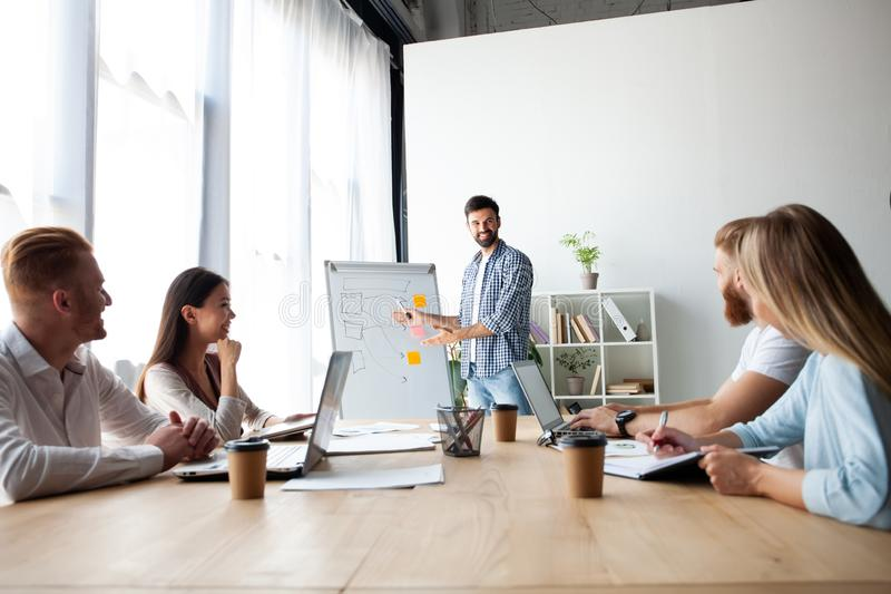 Achieving best results together. Modern young man conducting a business presentation while standing in the board room. royalty free stock images