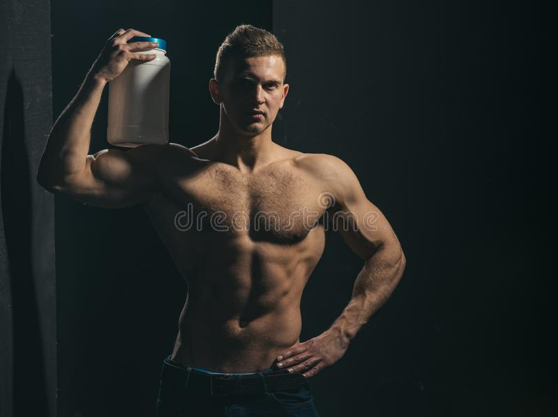 Achieving health and fitness goals. Healthy diet and fitness. Athletic man hold vitamin bottle in strong arms. Man use royalty free stock image