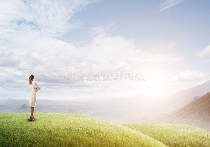 Achieving top of success. Elegant businesswoman standing on green hill and looking ahead royalty free stock images