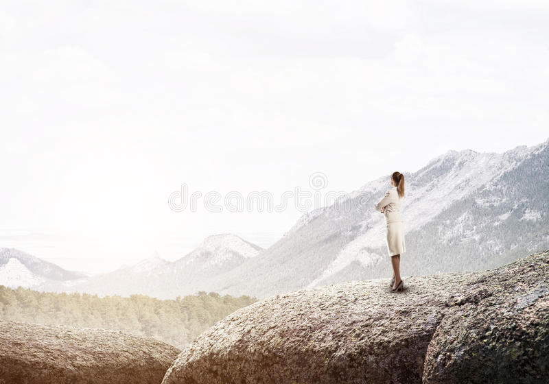 Achieving top of success. Elegant businesswoman standing on rock top and looking ahead royalty free stock image