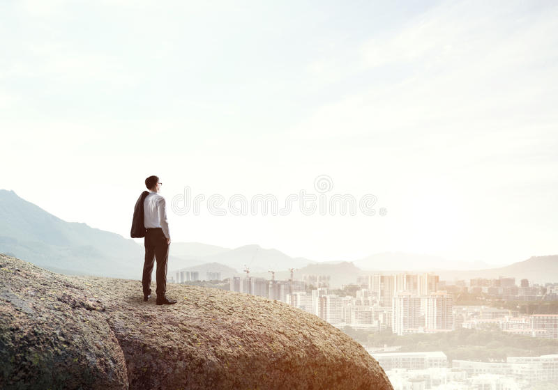 Achieving top of success. Elegant businesswoman standing on rock top and looking ahead stock photography