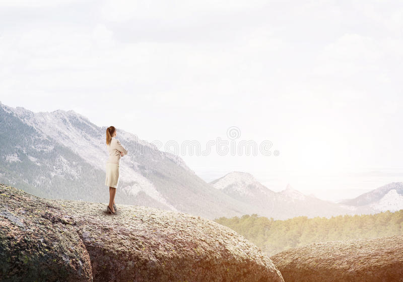 Achieving top of success. Elegant businesswoman standing on rock top and looking ahead stock photos