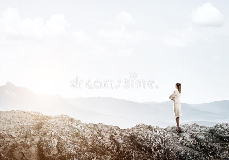 Achieving top of success. Elegant businesswoman standing on rock top and looking ahead stock photo