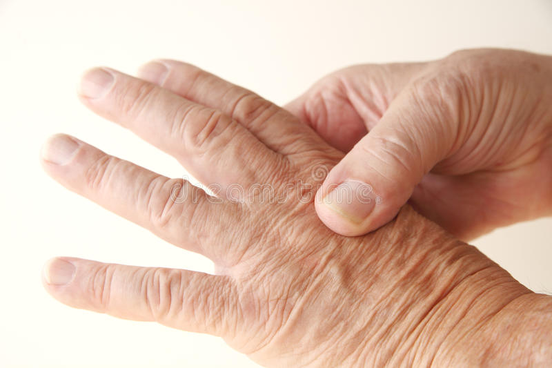 Aching knuckle on older man. Senior man massages the pain on a knuckle stock photo
