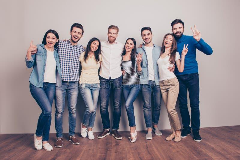 Acht glückliche Freunde werfen nahe der Wand auf, überrascht und gesturi stockfotografie