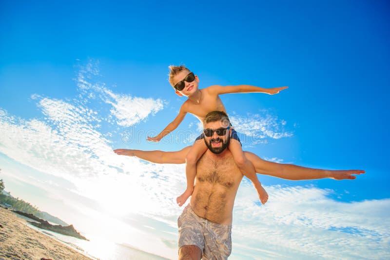 Acht Jahre alte Junge, die auf Vati ` s sitzen, schultert Beide in den Schwimmenkurzen hosen und -Sonnenbrille, Spaß auf dem Stra lizenzfreie stockbilder