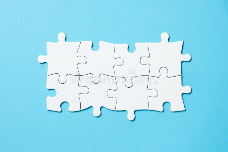 Acht stukken witte puzzel op blauwe achtergrond voor bedrijfspresentatie stock afbeelding