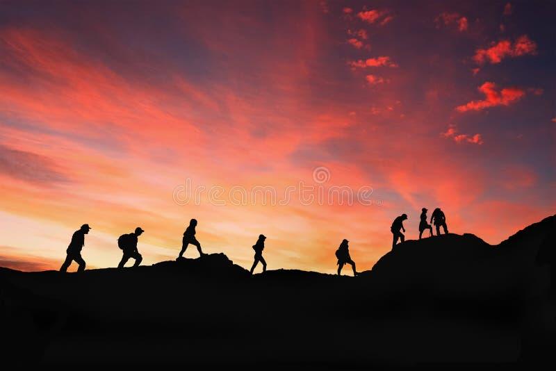 Acht vrienden lopen op bergweg in zonsondergang stock fotografie