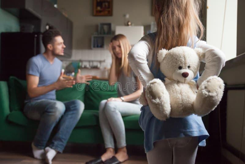 Achter de holdingsstuk speelgoed van het meningsmeisje terwijl ouders het vechten stock afbeelding
