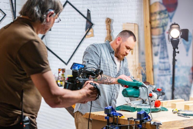 Achter de schermen van productie voor de video die van het cameramateriaal, de vastgestelde scène met de arbeider schieten royalty-vrije stock foto's
