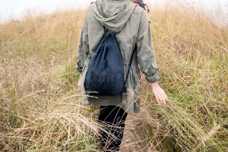 Achter jonge meisjesreiziger die met zak aan gouden weide op mo lopen royalty-vrije stock fotografie