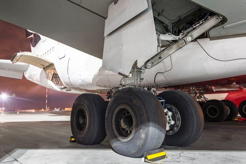 Achter landingsgestel van de wielen rekt het rubberband vliegtuigvliegtuigen, onder de nacht van de vleugelmening royalty-vrije stock fotografie