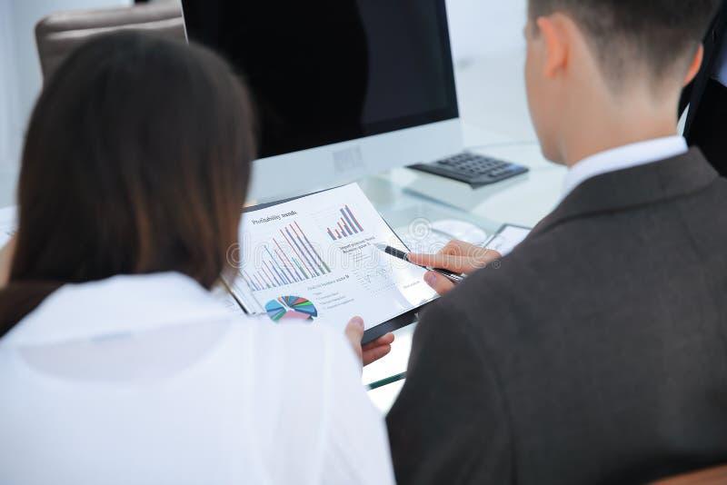 Achter mening commercieel team die met financiële documenten werken stock foto's