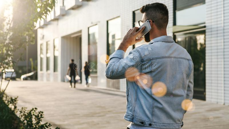 Achter mening De Hipsterzakenman met baard, in denimjasje en in glazen loopt rond stad en vraag op telefoon royalty-vrije stock afbeeldingen