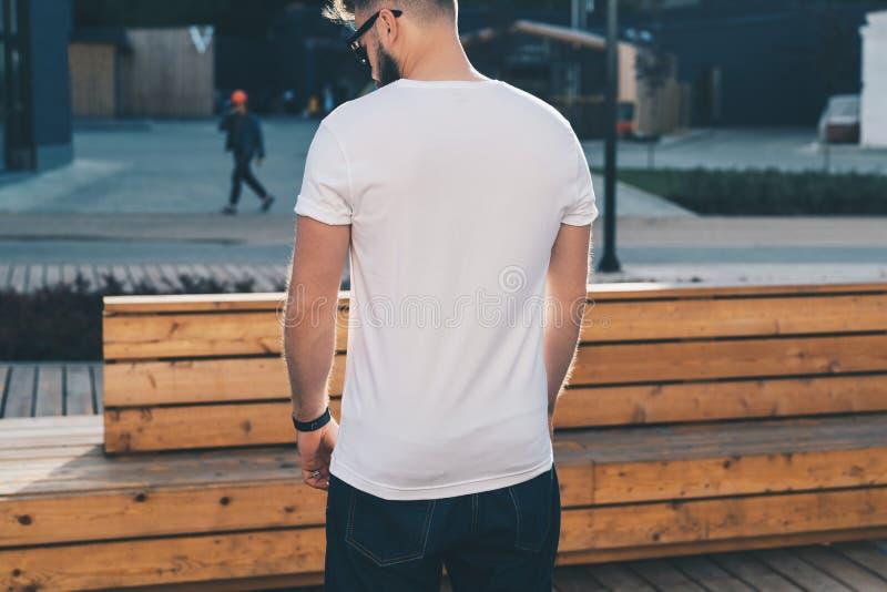Achter mening De jonge gebaarde hipstermens gekleed in witte t-shirt en zonnebril is tribunes op stadsstraat Spot omhoog royalty-vrije stock foto
