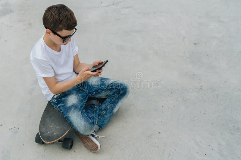 Achter mening De tiener zit op skateboard, gebruikt smartphone, digitaal gadget, de spelen van de spelencomputer, doorbladerend I stock foto's