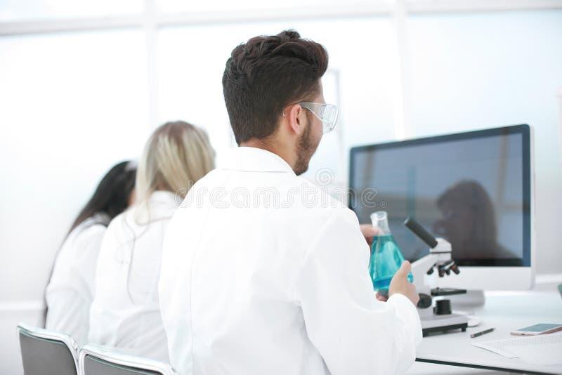 Achter mening een groep wetenschappers die in een modern laboratorium werken stock afbeelding