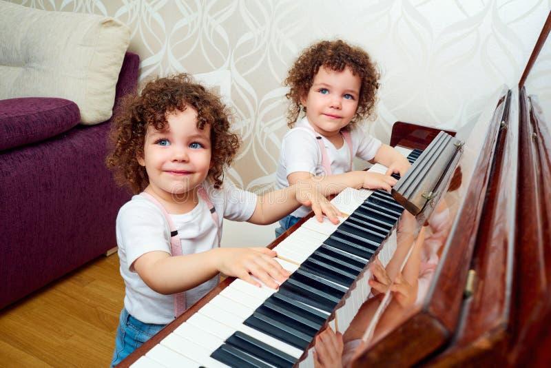 Achter mening Een kind bevindt zich voor de piano en speelt een melo stock foto's