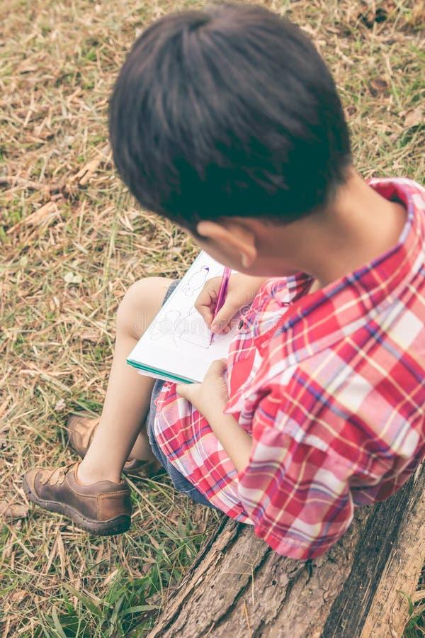 Achter mening Jongen die op notitieboekje schrijven Het concept van het onderwijs Uitstekend s stock foto's