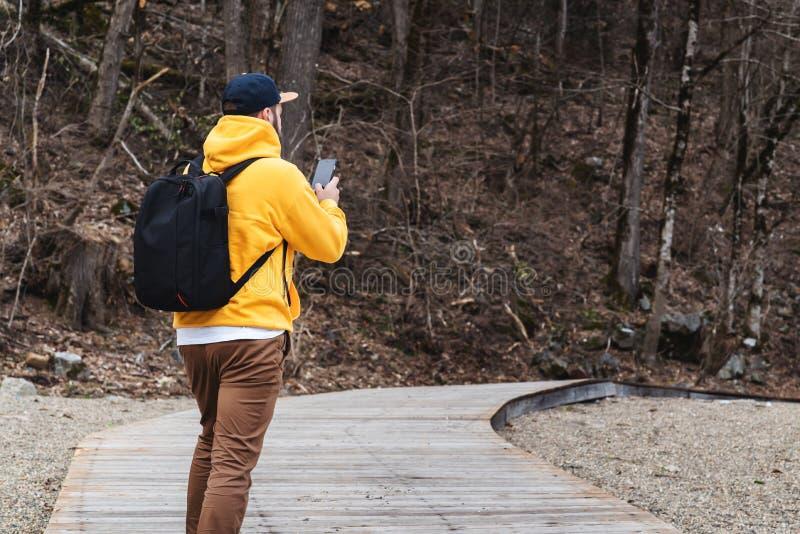 Achter mening Mensentoerist in gele hoodie met rugzaktribunes in openlucht, gebruikend smartphone De reizigersgangen, neemt foto  royalty-vrije stock afbeeldingen