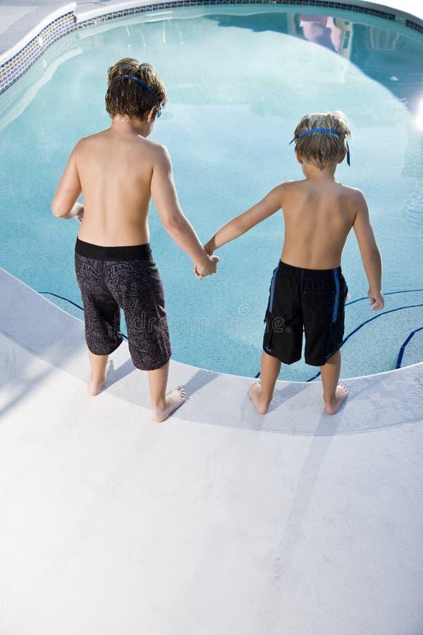 Achter mening van jongens die in zwembad kijken royalty-vrije stock afbeelding