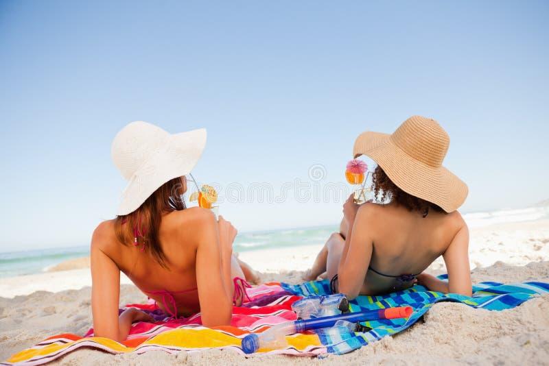 Achter mening van mooie vrouwen die terwijl het nippen van cocktails op het strand zonnebaden stock afbeeldingen