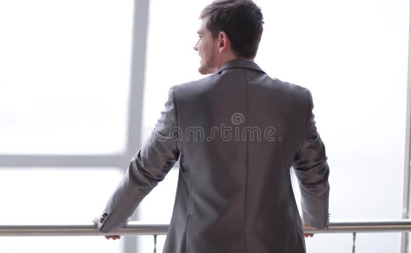 Achter mening zakenman in vrijetijdskleding die en zich dichtbij het bureauvenster bevinden denken stock afbeelding