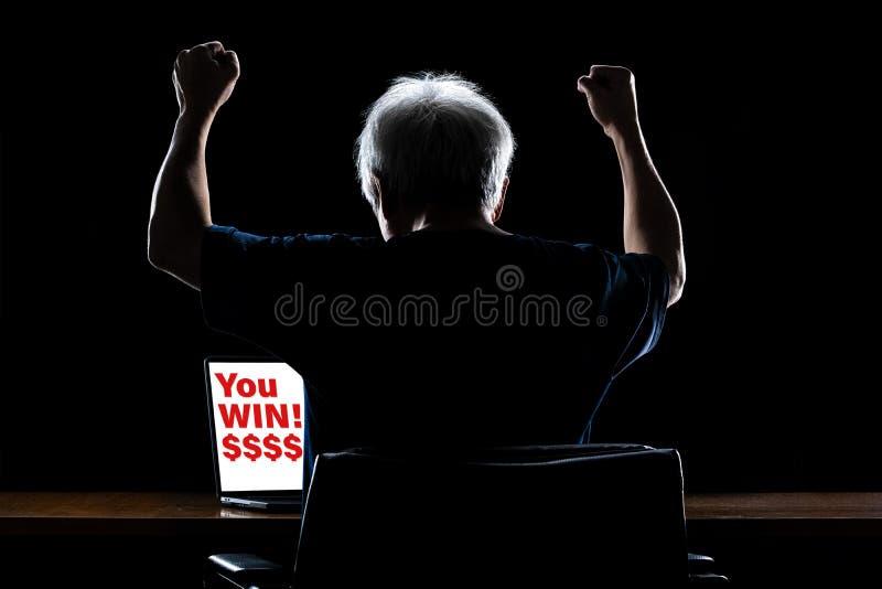 Achteraanzicht van een gelukkige man met grijs haar die zijn handen opstak in opwinding, kijkend naar zijn computerscherm met You royalty-vrije stock foto