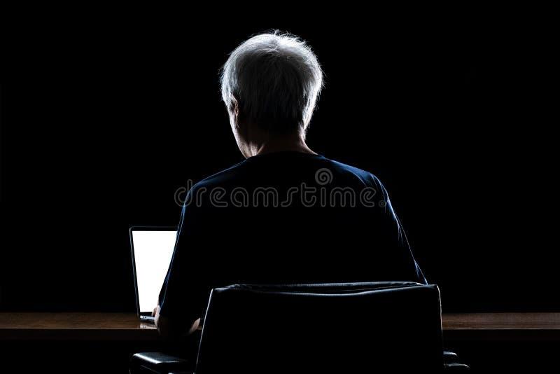 Achteraanzicht van een man met grijs haar die 's nachts 's avonds laat thuis werkt met zijn laptopcomputer royalty-vrije stock afbeelding