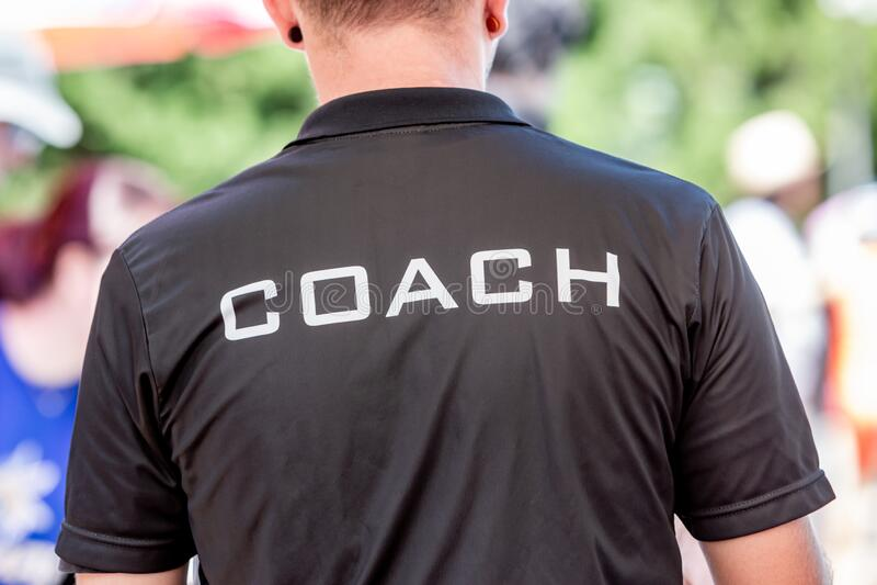 Achteraanzicht van een mannelijke coach met een zwart busshirt met het witte woord COACH, op achterzijde gedrukt royalty-vrije stock fotografie