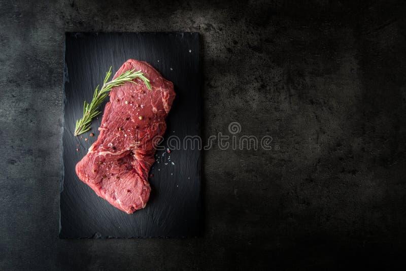 Achterdeellapje vlees Rundvlees ruw lapje vlees Rundvlees ruw lapje vlees met de de zoute slager en vork van de peperrozemarijn stock afbeelding